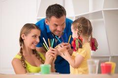 Dibujo y pintura felices preciosos de la familia en casa Fotos de archivo