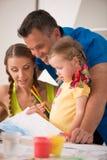 Dibujo y pintura felices preciosos de la familia en casa Imágenes de archivo libres de regalías