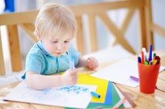 Dibujo y pintura lindos del niño pequeño con los rotuladores coloridos en la guardería Imagen de archivo