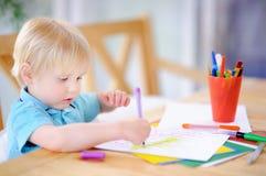 Dibujo y pintura lindos del niño pequeño con los rotuladores coloridos en la guardería Foto de archivo