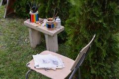 Dibujo y silla de los materiales de la foto en los cuales el lápiz de mentira bosqueja Foto de archivo
