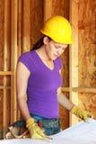 Dibujos arquitectónicos de repaso del trabajador de construcción de la mujer Foto de archivo