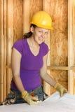 Dibujos arquitectónicos de repaso del trabajador de construcción de la mujer Imagen de archivo libre de regalías