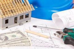 Dibujos de construcción eléctricos, herramientas y accesorios, pequeña casa y dólar de las monedas, concepto casero constructivo  Fotografía de archivo libre de regalías