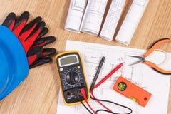 Dibujos eléctricos, multímetro para la medida en la instalación eléctrica y accesorios para los trabajos del ingeniero Fotos de archivo