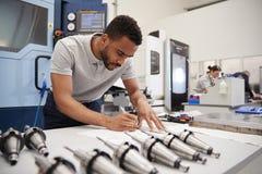 Dibujos masculinos de Measuring cad del ingeniero en fábrica imagen de archivo