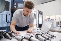 Dibujos masculinos de Measuring cad del ingeniero en fábrica fotos de archivo