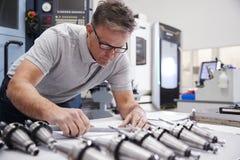Dibujos masculinos de Measuring cad del ingeniero en fábrica imágenes de archivo libres de regalías