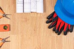 Dibujos o diagramas eléctricos, casco azul protector con los guantes y herramientas anaranjadas del trabajo Imagen de archivo libre de regalías