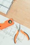 Dibujos o diagramas eléctricos, herramientas anaranjadas del trabajo para el uso en trabajos del ingeniero Imagen de archivo libre de regalías