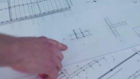 Dibujos profesionales del primer del nuevo proyecto existencias Las manos de los ingenieros profesionales que analizan dibujos de almacen de metraje de vídeo