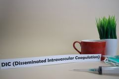 DIC  Disseminated Intravascular Coagulation text, grass pot, coffee cup, syringe, and face green mask. Healtcare/Medical and Business concept stock photography