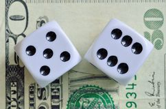 Dice. Closeup of a pair of dice with eleven showing on a fifty dollar bill stock photography