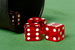 Dice. Red dice thrown from dice cup onto felt table royalty free stock images