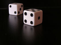 Dice. Closeup of white die on black reflective surface stock photos