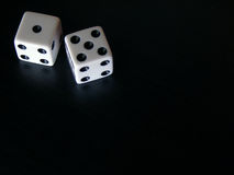 Dice. Overhead of die on reflective black surface stock images