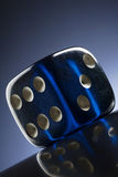 Dice. A transparent blue dice on dark bluie background Royalty Free Stock Photos