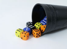 Dice and Black Cup. Black dice cup with multi-colored dice spilling out onto white background Royalty Free Stock Photography