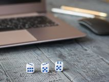 Dice with blue dots, notebook and pens on a wooden table. The concept of gambling online stock photos