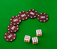 Dice and chips. Three dice with value six and some black chips over green carpet Stock Photography