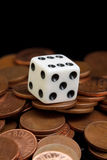 Dice and coins. A white dice on the cooper coins Royalty Free Stock Photo