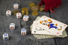 Dice, coins and cards Joker on a wooden game table. The concept of gambling Royalty Free Stock Photos