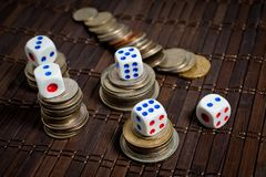 Dice and coins of different countries on a dark background royalty free stock photo