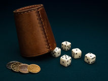 Dice, coins and leather cup. Royalty Free Stock Photography