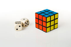 Dice and cube. Two dice and a rubik's cube on white background royalty free stock image