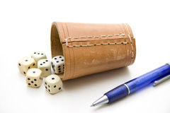 Dice cup. With die and ball-point pen royalty free stock image