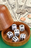 Dice cup. Five dice with a wooden dice cup Royalty Free Stock Image