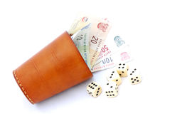 Dice cup with money. An old used brown leather dice cup with South African money (Rands) inside and dice lying around. Image isolated on white studio background Royalty Free Stock Images