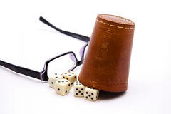 Dice cup with reading glasses. On white background Royalty Free Stock Image
