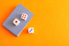 Dice and a deck of cards. A collection of dices on top of a pack of playing cards Stock Images