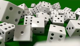Dice dynamic motion closeup DOF shot of dice rolling on green felt tabletop Royalty Free Stock Photo