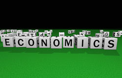 Dice economics. Dice on a green carpet making the word economics Royalty Free Stock Image