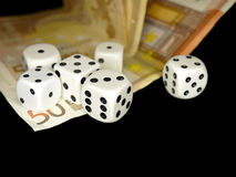 Dice and European banknotes money on black background, gambling Royalty Free Stock Photos