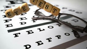 Dice with eye test written on it falling onto eye test Stock Photography