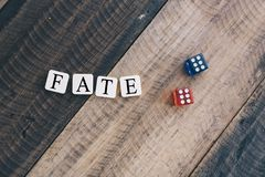 Dice of fate. A pair of dice with letter blocks forming the word 'fate' on wood background royalty free stock photos