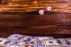 Dice in a flight above the one hundred dollar bills. Gamble conc Stock Photos