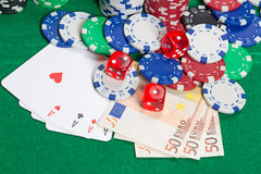 Dice, four aces, colorful poker chips and euro banknotes on a gr Royalty Free Stock Image