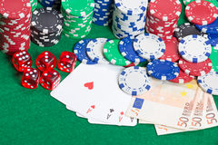 Dice, four aces, colorful poker chips and money on a green felt Stock Photos