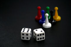 Dice with Game Pieces on Black. Dice in the foreground with multi-colored game pieces in the background on a textured black surface royalty free stock photos