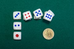 Dice and gold dollar on the green baize Royalty Free Stock Photos