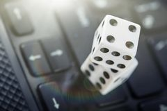 Dice on laptop computer keyboard. Сoncept of online gambling and online casino. Creative idea with devil`s bones and PC keyboard.