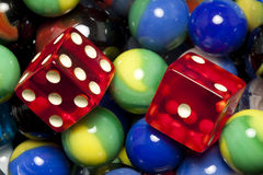 Dice & Marbles. Red dice on top of marbles Royalty Free Stock Photos