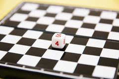 Dice with numbers on the background of the chessboard stock images