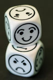 Dice with opposite sad and happy emoticon sides Royalty Free Stock Photography