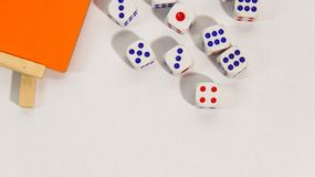 Dice and orange board on white background royalty free stock image