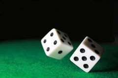Dice over green felt. Pair of dice rolling over green felt Royalty Free Stock Images